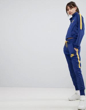 Nike Желто-синие спортивные брюки с завышенной талией. Цвет: синий