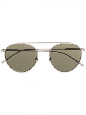 Солнцезащитные очки в круглой оправе Lacoste. Цвет: серебристый